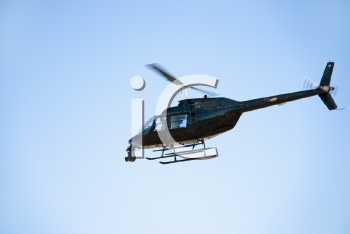 Royalty Free Photo of a Low Angle Shot of a Helicopter Flying Through the Sky