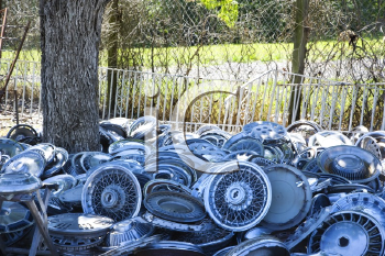 Royalty Free Photo of Stacks of Old Hubcaps on the Ground Next to a Tree