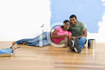 Royalty Free Photo of a Couple Relaxing Together With Wine Next to a Half-Painted Wall