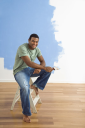 Royalty Free Photo of a Young Man Sitting Next to a Half-Painted Wall Holding a Paintbrush