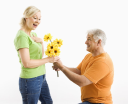 Royalty Free Photo of a Man on Bended Knee Giving a Woman a Bouquet of Yellow Flowers