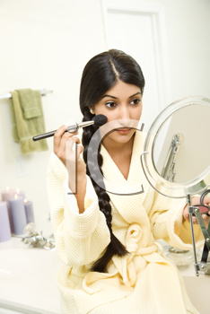 A young woman wearing a bathrobe is sitting on the bathtub  in front of a mirror and applying makeup. Her long dark hair is braided and hanging over her shoulder. Vertical shot.