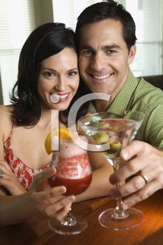 Couple raise their drinks to the camera. Vertical shot.