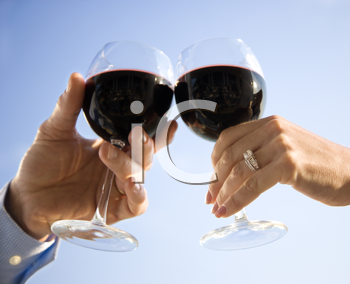 A married couple's hands toasting with red wine. Horizontal shot.