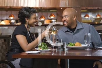 African-American couple dining out. They are toasting with glasses of white wine and smiling. Horizontal shot.