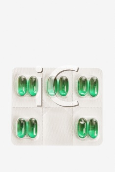 Green capsule tablets in an individual dose package. Vertical shot. Isolated on white