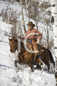 Cowboy in chaps riding a horse in the snow. Vertical shot.