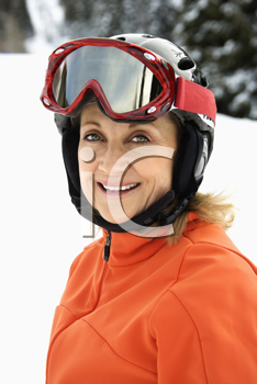 Closeup of smiling female skier wearing red goggles and orange ski jacket. Vertical shot.