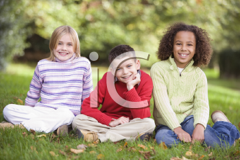 Royalty Free Photo of Three Children Sitting in a Park