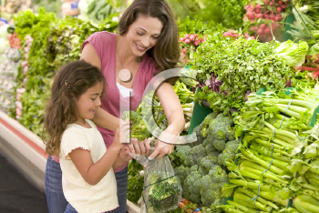 Royalty Free Photo of a Mother and Daughters Shopping for Broccoli