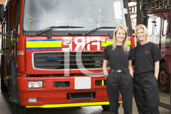 Royalty Free Photo of Two Female Firefighters in Front of the Truck