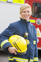 Royalty Free Photo of a Firefighter Standing by the Fire Engine