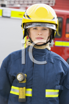 Royalty Free Photo of a Firefighter Beside a Firetruck