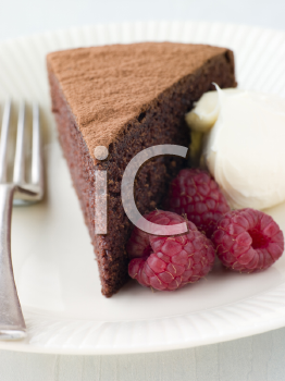 Royalty Free Photo of a Chocolate Sponge Cake With Whipped Cream and Raspberries