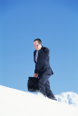 Royalty Free Photo of a Man Walking on a Snowy Mountain Talking on a Cellphone