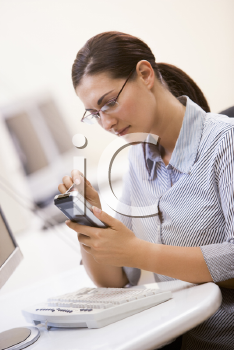 Royalty Free Photo of a Woman at a Computer With a PDA