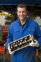 Royalty Free Photo of a Mechanic Holding a Car Part