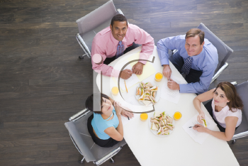 Royalty Free Photo of People in a Boardroom With Sandwiches
