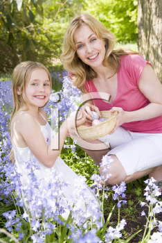 Royalty Free Photo of a Woman and Daughter Looking for Easter Eggs