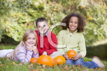 Royalty Free Photo of Three Friends With Pumpkins