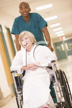 Royalty Free Photo of an Orderly Pushing a Woman in a Wheelchair