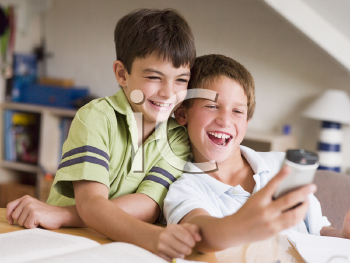 Royalty Free Photo of Two Boys Playing With a Cellphone