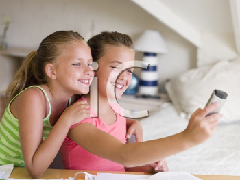 Royalty Free Photo of Two Girls Taking a Picture With a Cellphone