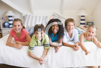 Royalty Free Photo of Five Friends on a Bed