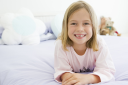 Royalty Free Photo of a Little Girl Lying on a Bed