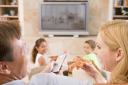 Royalty Free Photo of a Family Eating Pizza in Front of the TV