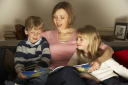 Royalty Free Photo of a Mother Reading to Her Children
