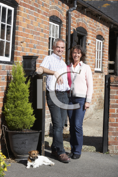 Royalty Free Photo of a Farmer and Wife Outside Their Home