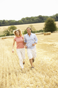Couple Running Together Through Summer Harvested Field