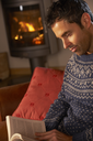 Middle Aged Man Relaxing With Book By Cosy Log Fire