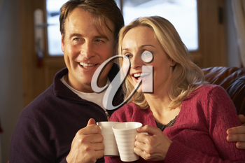 Middle Aged Couple Sitting On Sofa With Hot Drinks Watching TV