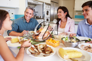 Family Sitting Around Table At Home Eating Meal