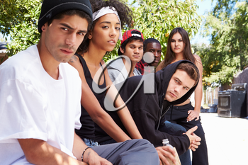 Gang Of Young People In Urban Setting Sitting On Bench