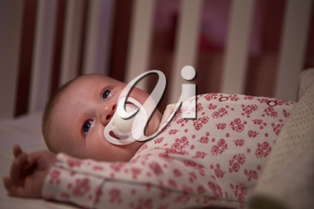 Baby Girl With Pacifier Lying In Cot