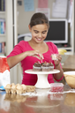 Girl Decorating Homemade Cupcakes In Kitchen