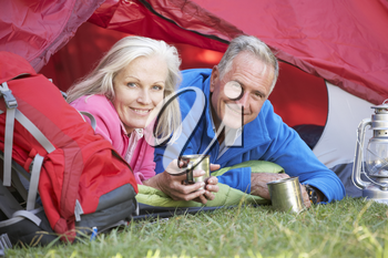 Senior Couple Inside Tent On Camping Holiday