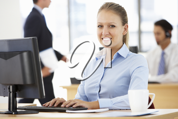 Businesswoman Working At Desk In Busy Office