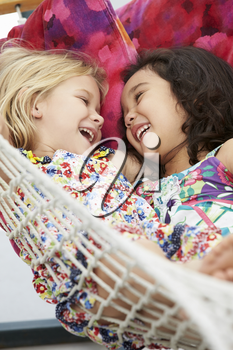 Two Young Girls Relaxing In Garden Hammock Together