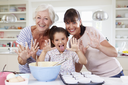 Grandmother, Granddaughter And Mother Baking Cake In Kitchen