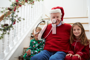 Grandfather With Grandchildren Sits On Stairs At Christmas