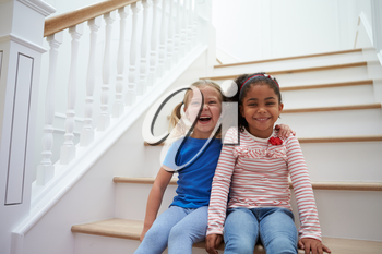 Portrait Of Two Girls Playing Game On Staircase At Home