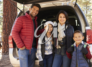 Portrait family outdoors standing at the open back of car