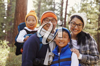 Portrait of an Asian family of four in a forest setting