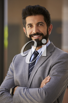 Smiling Hispanic businessman, arms crossed, close up vertical
