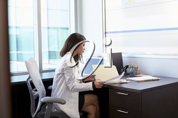 Female Doctor Wearing White Coat Reading Notes In Office