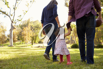 Couple walking in park with their young daughter, back view